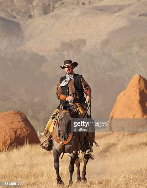 Cowboy rides horse between two large boulders