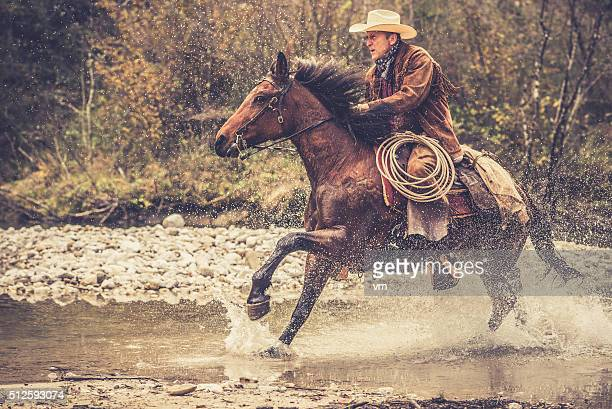 Cowboy riding across a river in the forest