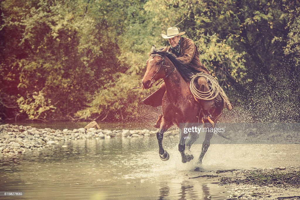 Cowboy riding across a river in the forest : Stock Photo