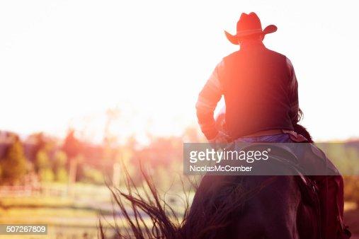 Cowboy riding away rear view