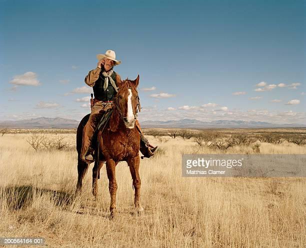 Cowboy riding horse using mobile phone
