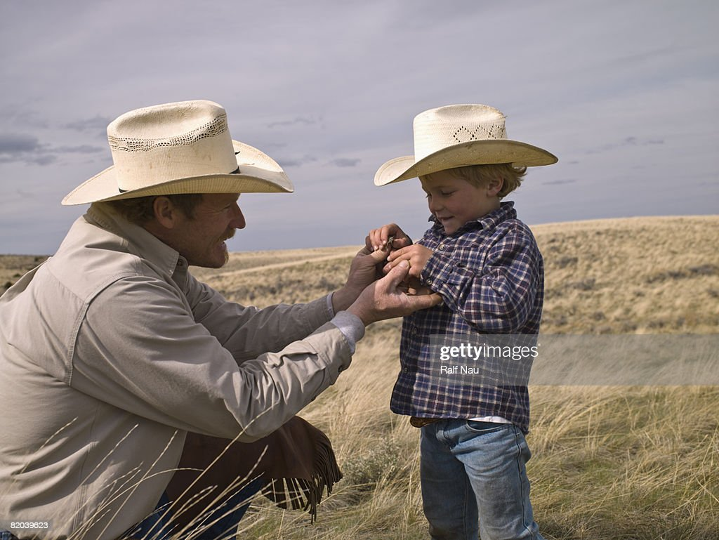 Cowboy showing child insect : Stock Photo