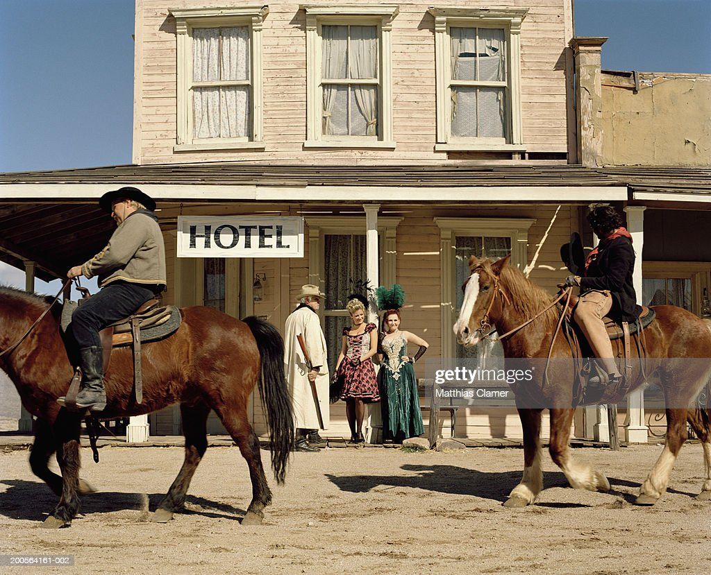 Cowboy standing with showgirl with other cowboy riding horse : Stock Photo