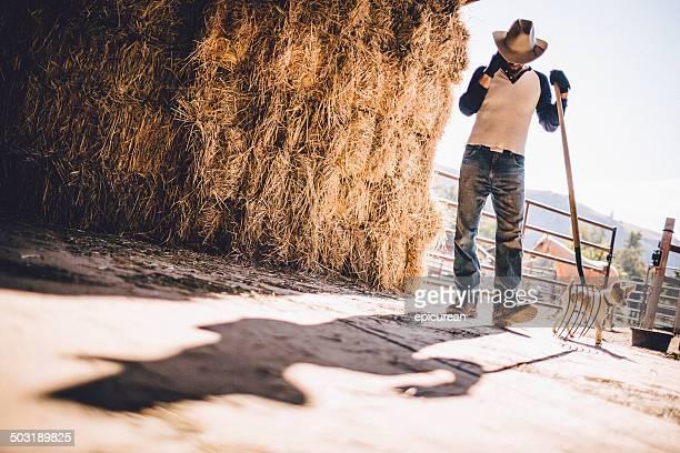 Cowboy ist mit Heugabel von Heuhaufen auf Scheune