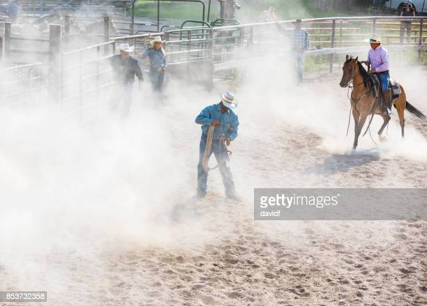 Cowboy Surrounded By Dust While Tying a Rope at a Rodeo