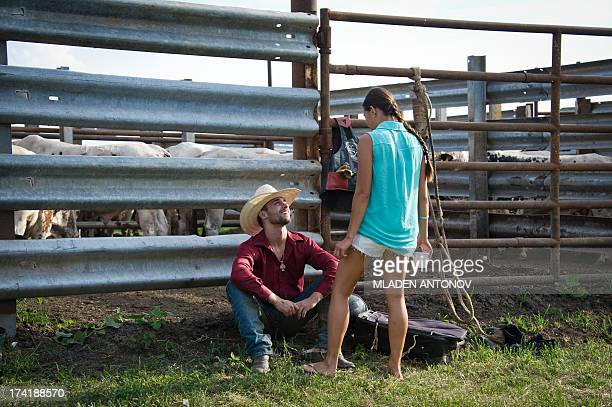 A cowboy talks to a girl before the 'Battle of the Beast' bull riding competition at J Bar W ranch in Union Bridge Maryland on July 20 2013...