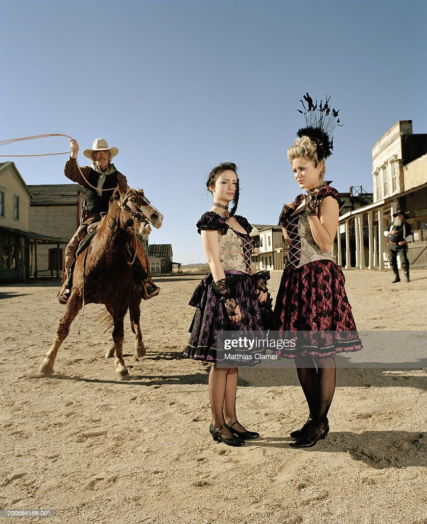 Cowboy throwing lasso rope with showgirls standing in foreground : Stock Photo