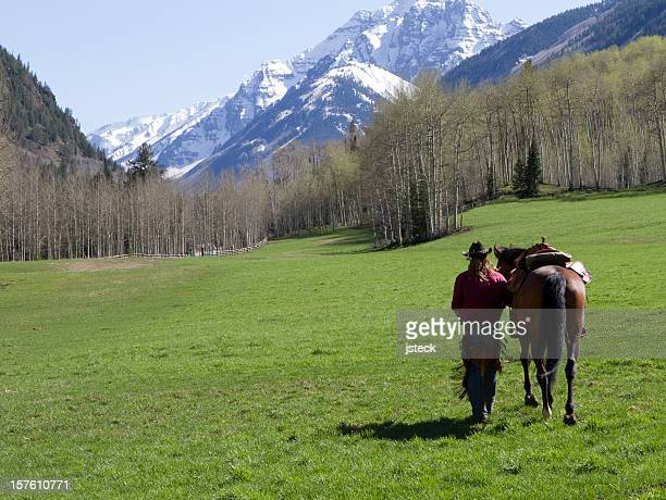 Cowboy Walking His Horse in Open Mountain Field