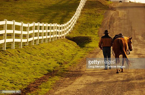 Cowboy walking with horse, rear view