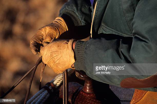 A cowboy wears his leather gloves while riding his horse in 1996 on the Double Mountain River Ranch outside Rotan TX Cowboy life in 1996 was much the...