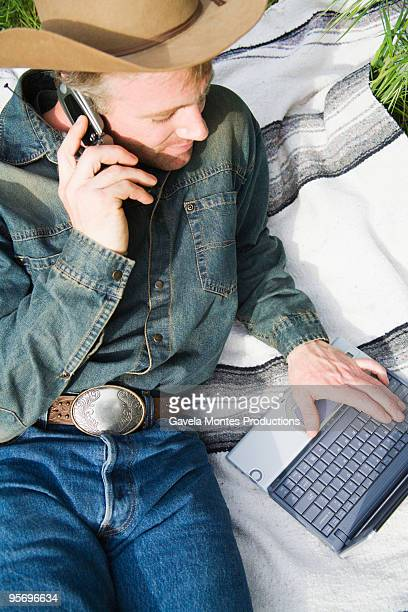 Cowboy with a cell phone and laptop computer