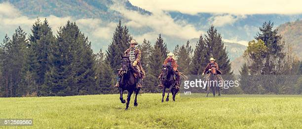 Cowboys and cowgirl riding their horses across a meadow