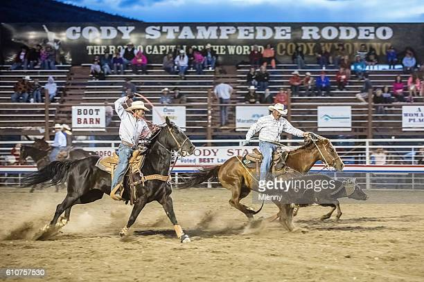 Cowboys chasing bull with lasso at Rodeo Cody Wyoming