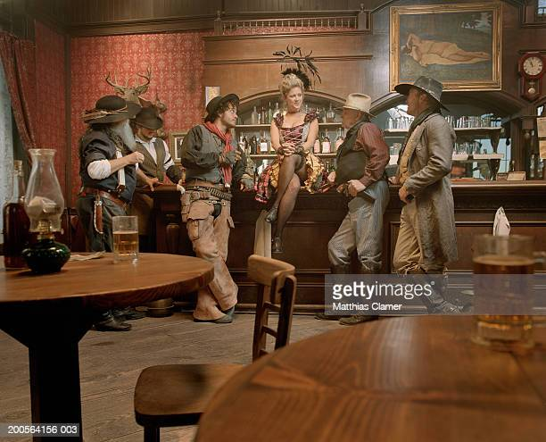 Cowboys flirting with showgirl in saloon