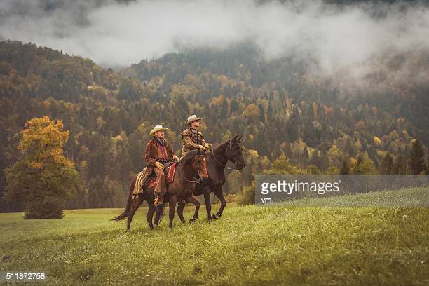 Cowboys riding across a meadow in the forest