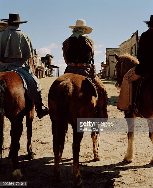 Cowboys riding horses through town, rear view