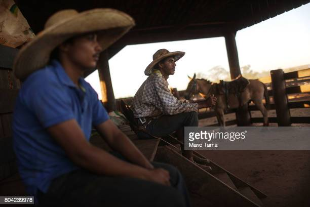 Cowboys sit in a corrall at a cattle feed lot in the Amazon on June 28 2017 near Chupinguaia Rondonia state Brazil The confinement farm currently...