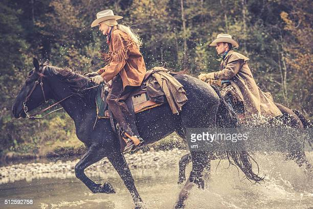 Cowgirl and cowboy riding across a river in the forest