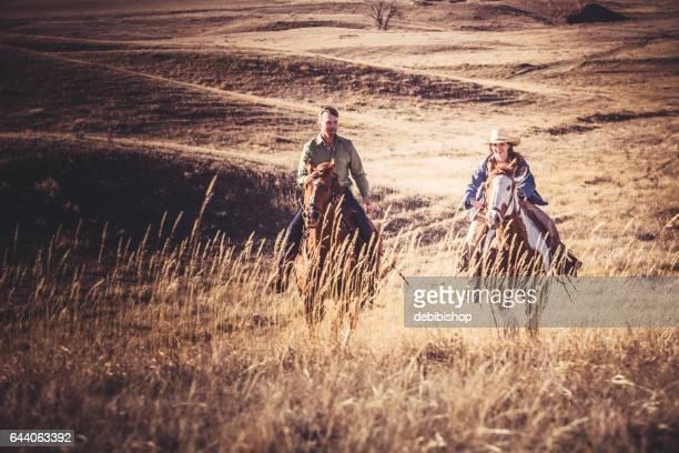 カウガールとカウボーイの馬に一緒に乗って