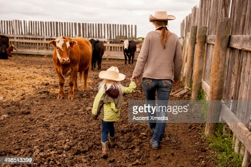 Cowgirl and daughter walk through cow paddock : Foto de stock