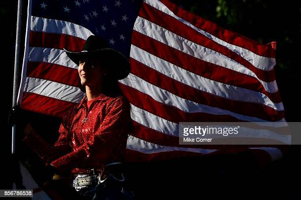A cowgirl carries the US flag during the North Carolina State Wolfpack Walk of Champions prior to the football game at Carter Finley Stadium on...