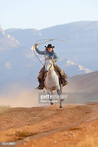 Cowgirl galloping with lasso in hand.