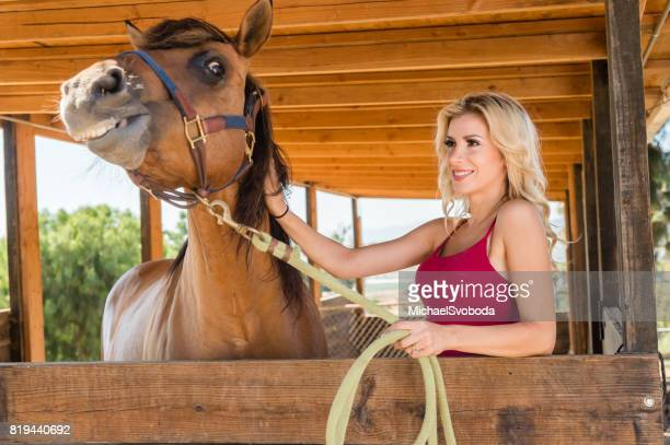 Cowgirl In The Stables With Her Horse
