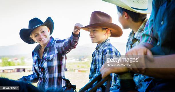 Cowgirl mother replacing son's cowboy hat while horse riding