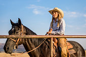 A young cowgirl on a horse looking determined