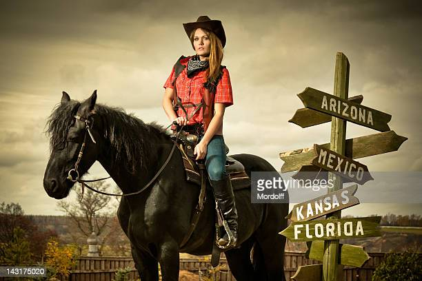 Cowgirl on black horse at road sign