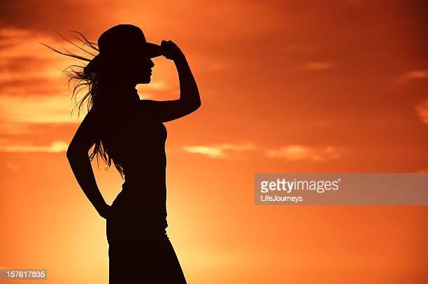 Silhouette da Cowgirl In un cielo arancione caldo occidentale