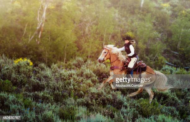 Cowgirl speeding through sagebrush