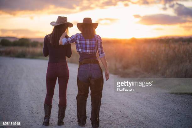 Cowgirl walking on the road