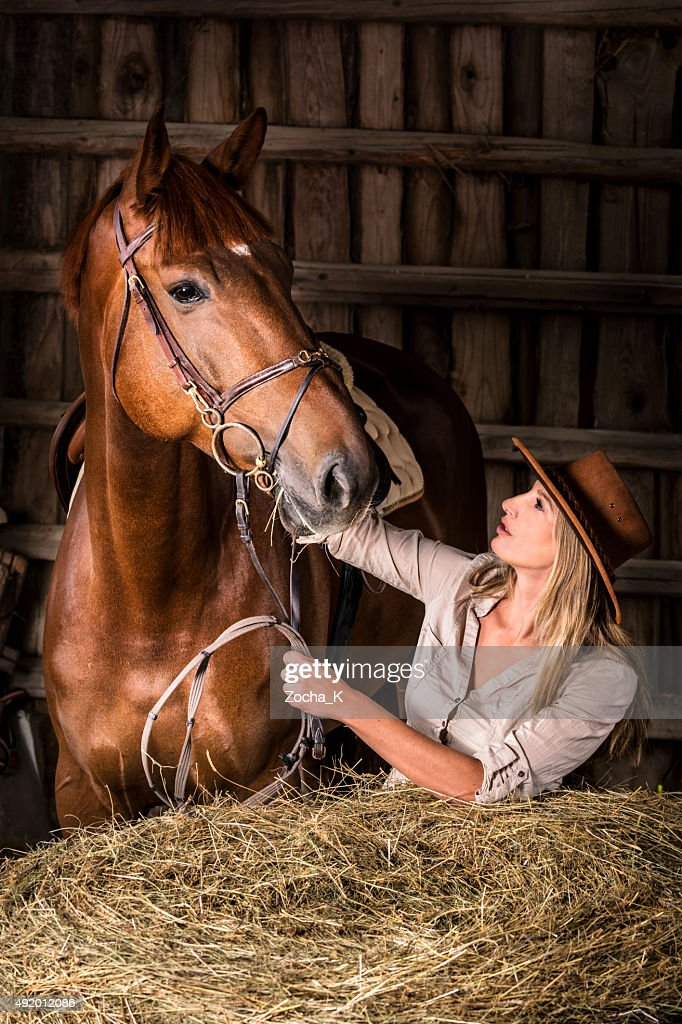 Cowgirl with her horse in barn next to hay bales