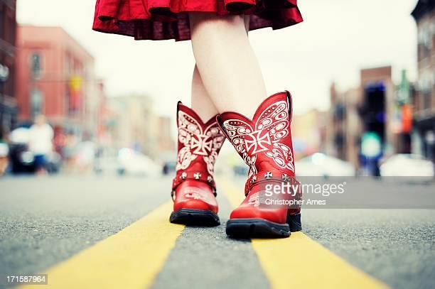 Cowgirl mit roten Schuhen auf der Straße