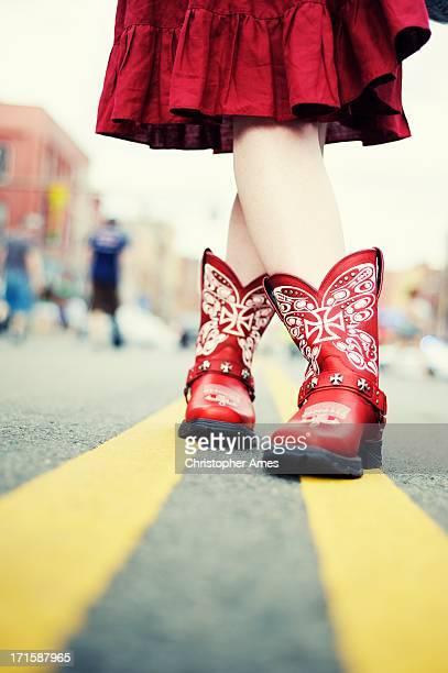 Vaqueira com botas vermelho na estrada