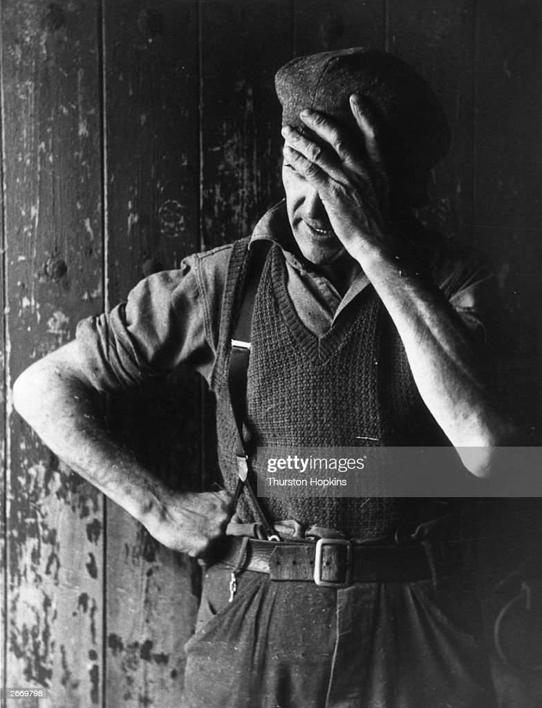 Cowman Joe Fry with his head in his hand after a twelve-hour shift at White Carr Farm, Kirkham, Lancashire. Original Publication: Picture Post - 7392 - The Men Who Never Strike - pub. 1954
