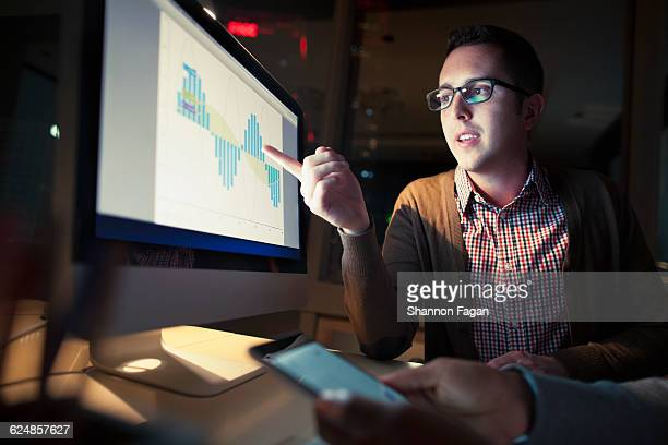 Coworker discussing findings on screen at night
