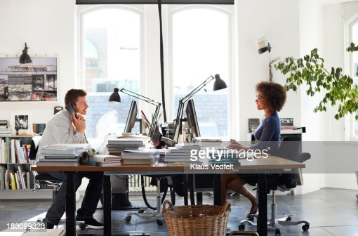 Coworker on phone while colleague is talking : Stock Photo