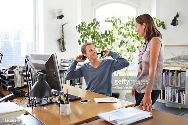 Coworker taking of headphone when colleague appear