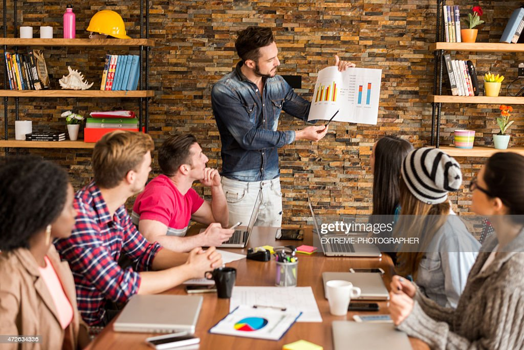 Coworkers analyzing data chart in the office : Stock Photo