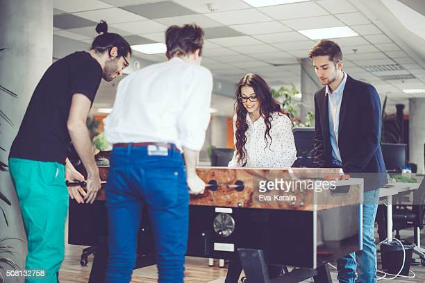 Coworkers are playing foosball at work