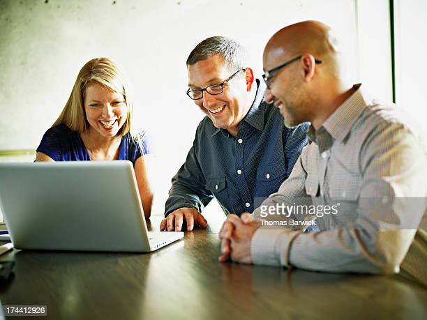 Coworkers at laptop in office conference room