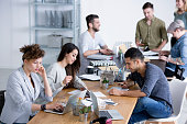 Young diverse female and male coworkers brainstorming ideas for a project by a table at a start-up office