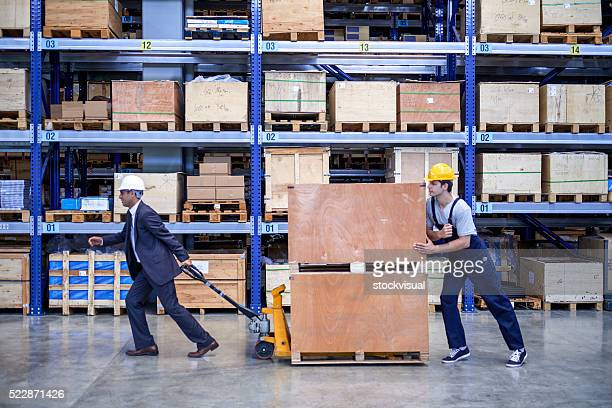 Coworkers carrying cardboard box in warehouse.