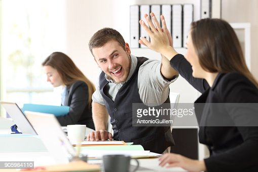 Coworkers celebrating achievement at office : Stock Photo