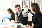 Two excited coworkers celebrating achievement giving five at office