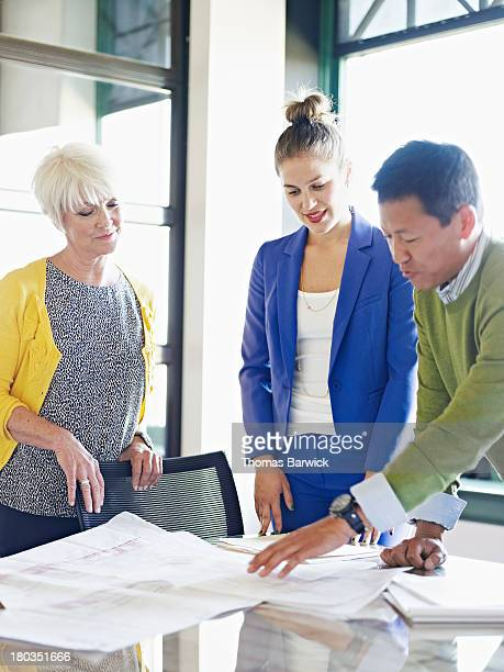 Coworkers discussing plans in conference room