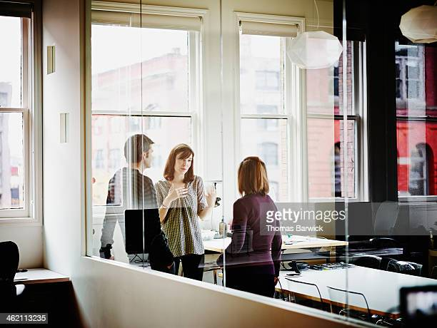 Coworkers discussing project in corner office