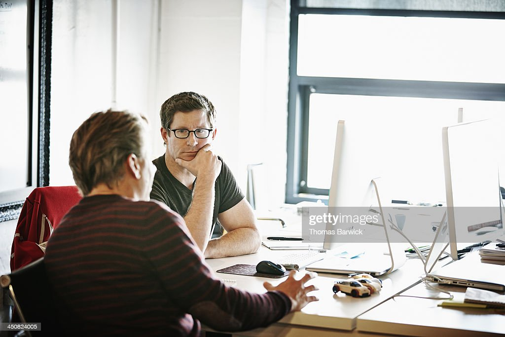 Coworkers discussing project in high tech office : Stock Photo